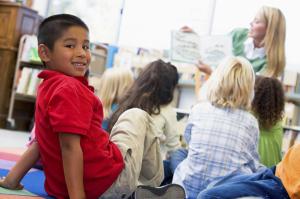 Latchkey teacher reading to children in library, boy looking